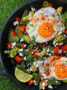 mexican eggs with lime and feta cheese in a black skillet