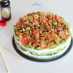 A black plate with a sushi cake, seaweed wraps are used as layers
