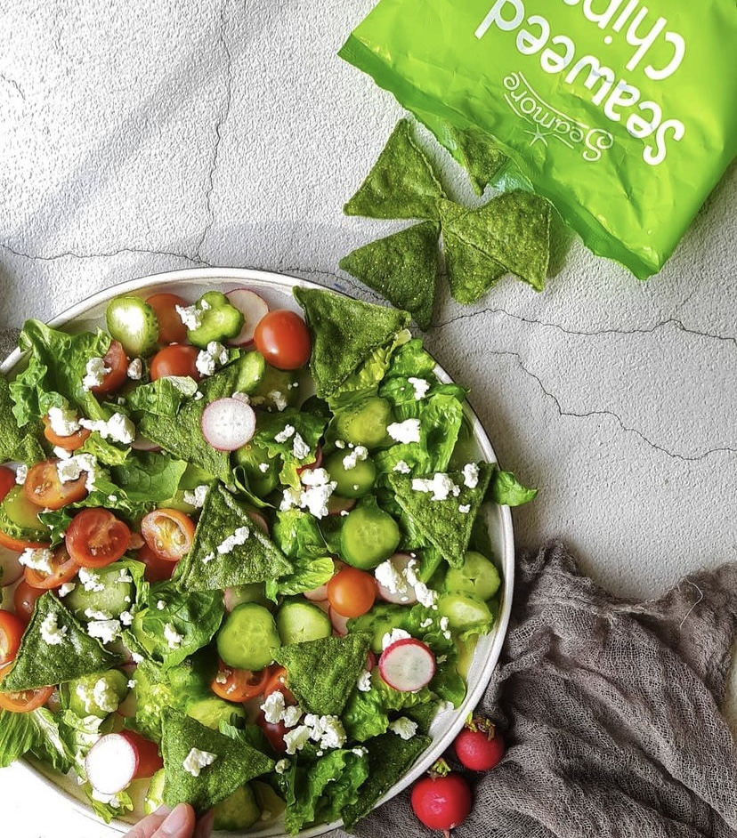 colorful fattoush salad with a bag of seaweed chips on a white table