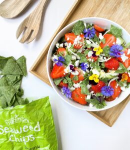 strawbery salad with seaweed chips, strawberries, avocado, and edible flowers