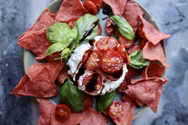 a plate of red seaweed chips with basil over cottage cheese