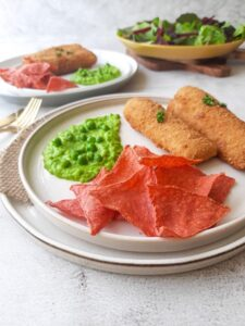 fish and chips with red seaweed chips and green vegetables on a plate