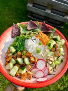 A poke bowl served on a plate with a grass background